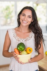 Beautiful brunette holding vegetables bowl
