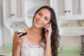 Pretty brunette on the phone having glass of wine