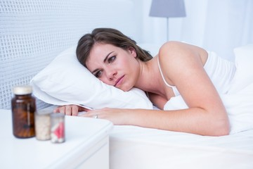 Sad woman looking at pills in bed