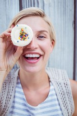 Pretty blonde woman grimacing with cupcake