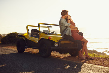 Couple on road trip sharing a romantic kissing