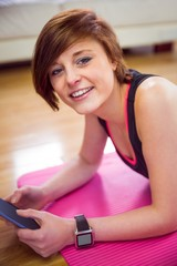 Fit woman looking at camera and using tablet pc on mat