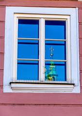 Kirchturm spiegelt sich in einem Fenster