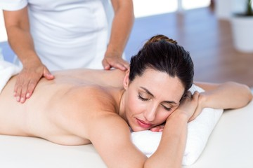 Relaxed brunette receiving back massage