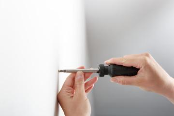 Worker manually tightening hang screw