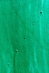 Green painted metal sheet with rivets diagonally