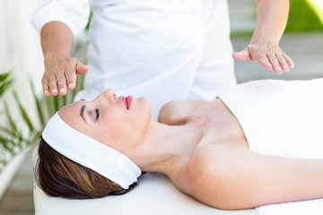 Calm woman receiving reiki treatment