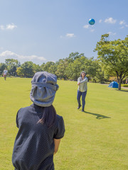 公園でソフトバレーボールして遊ぶ親子