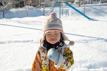 雪が積もった公園で遊ぶ子供