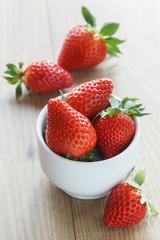 Frische Erdbeeren in einer Schale, auf Holz