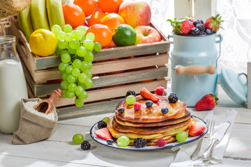 Sweet pancakes with fruits and maple syrup