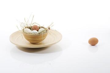 Eier in Holzschale auf Teller, braunes Ei abseits