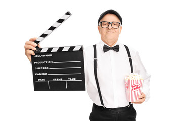 Movie director holding a clapperboard and popcorn