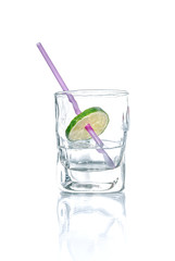 Vodka with lime and drinking straw in a glass