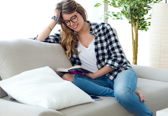 Beautiful young woman reading a book in the sofa.