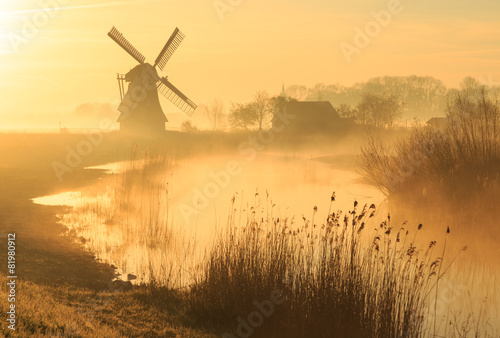 Plagát Windmill during a foggy, yellow sunrise in the countryside.