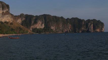 panorama of city beach with moored thai longtail boat