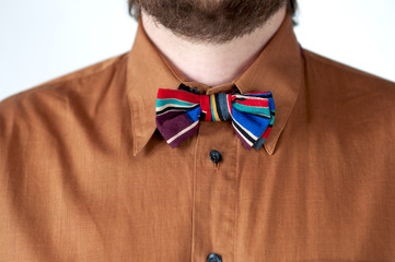 Colorful striped  bow tie with brown shirt  on men's neck.