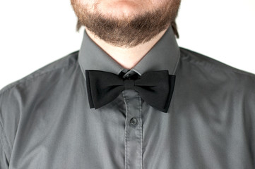 Black  bow-tie with gray shirt on men's neck. Strict dress code.