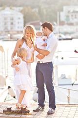 Happy family having fun walking on the mooring near yachts