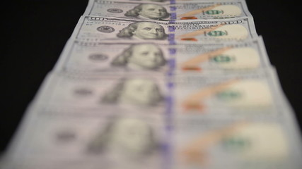 Money Dollars Denominations are fanned out on a black table