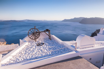Old, wooden water pump wheel on a roof in Oia, Santorini