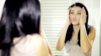 Woman talking to herself getting angry in front of mirror