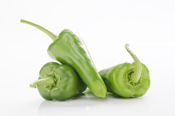 fresh green chilies on white background display