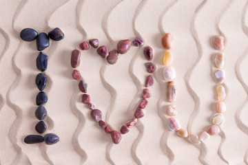 I Love You in colorful stones on golden beach sand