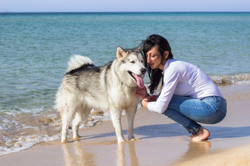Brunette girl with her dog on beach