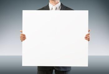 Holding. Businessman holding blank sign