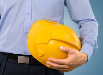 Engineering. Close-up shot of a foreman holding a hardhat on the