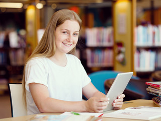 Teenage girl with tablet in library
