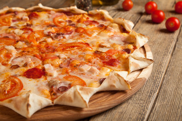 "Italian pizza ""Bavarian"" on a wooden table."