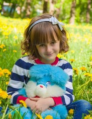 little smiling girl sitting on lawn with  toy in her hands