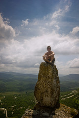 man sitting on a top of stone in mountains