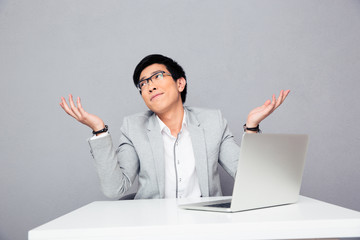 Businessman sitting at the table and shrugging