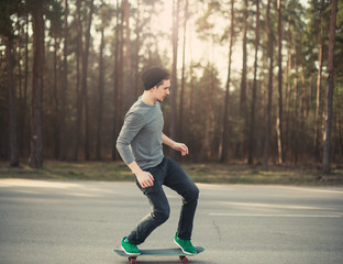 male skateboarder skating in the park at sunset