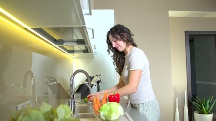 Happy young woman in the kitchen washing vegetables