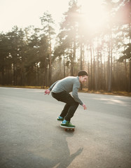hipster boy skateboarder riding a skateboard in the park