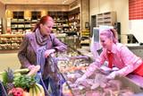Verkäuferin an Fleisch- u. Wursttheke bedient Kundin