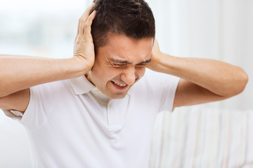 unhappy man closing his ears by hands at home