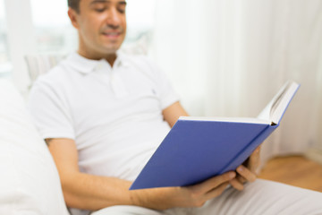 close up of happy man reading book at home