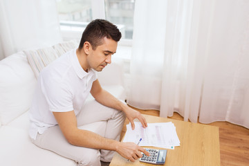 man with papers and calculator at home