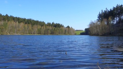 Spring landscape with lake, forest and blue sky