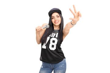 Female hip-hop artist singing on a microphone