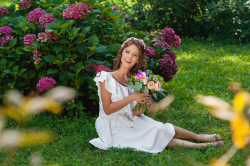 Beautiful woman with a wedding bouquet of flowers sitting
