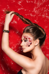 creative fashion girl with long hair with red stones on the face