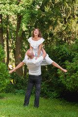 A man raises a woman in her arms, and she does the splits