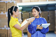 two chinese female workers in warehouse - 81999154